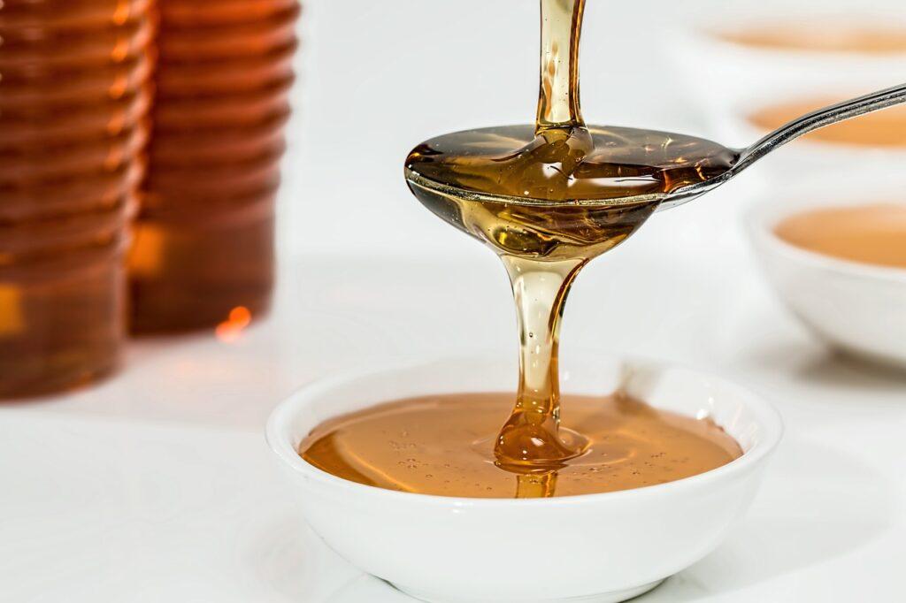 Auf einem Teelöffel wird Honig geträufelt