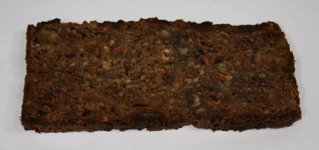 Eine Scheibe Essener Brot liegt auf einem weißen Untergrund.