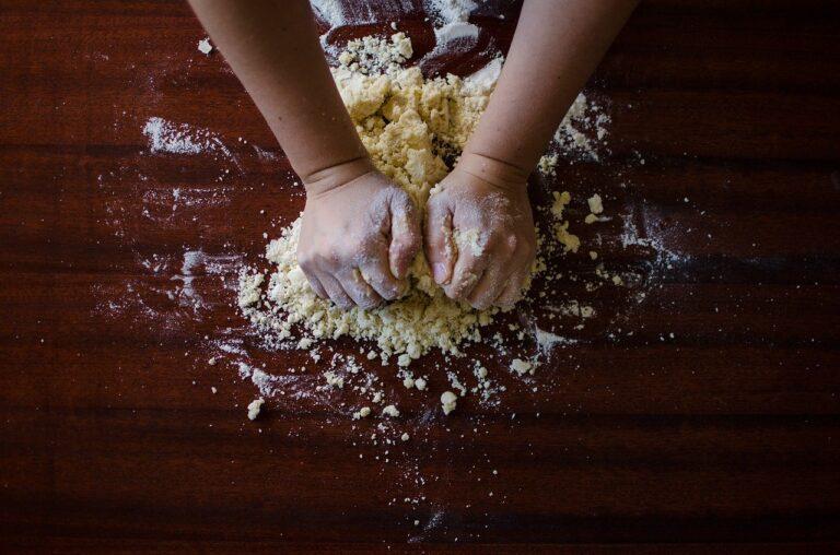 Auf einer dunklen Holzoberfläche mit Mehl kneten zwei Hände einen Teig.