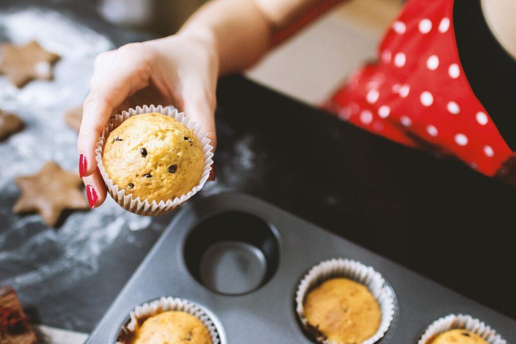 Jemand hält einen Muffin über einem Muffinblech mit weiteren Küchlein hoch.