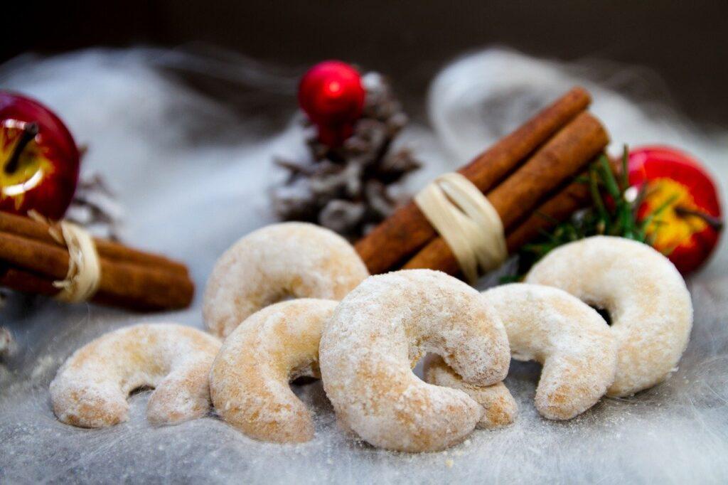 Vor weihnachtlicher Deko liegen einige Vanillekipferl.