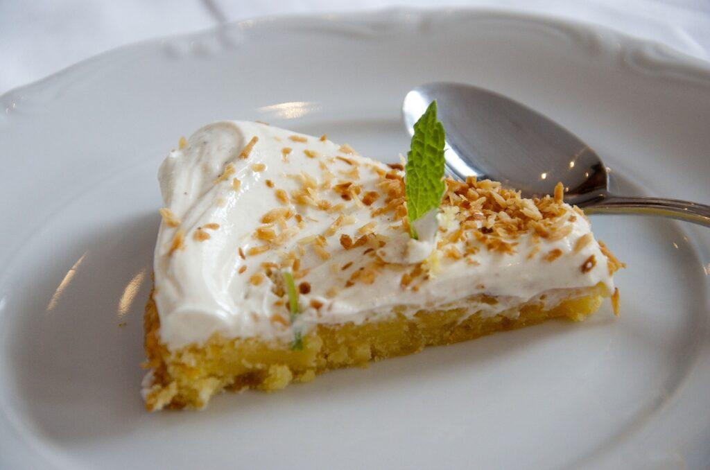 Auf einem weißenTeller neben einem Löffel liegt ein Stück Cheesecake.