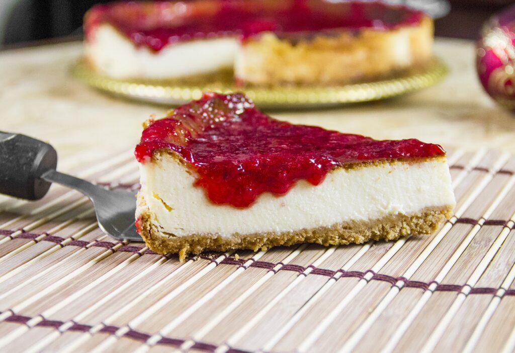 Auf einem Kuchengitter steht ein Stück Käsekuchen, von dem rotes Fruchtpüree heruntertropft