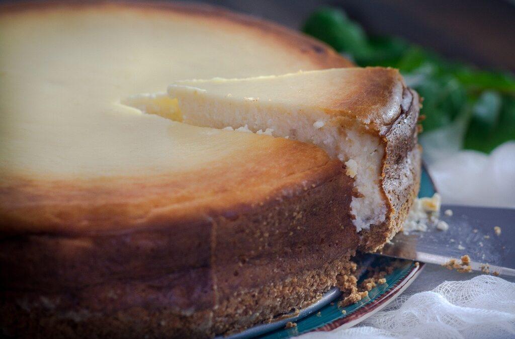 Ein Käsekuchen wurde angeschnitten und gerade hebt jemand mit einem Tortenheber ein Stück heraus.