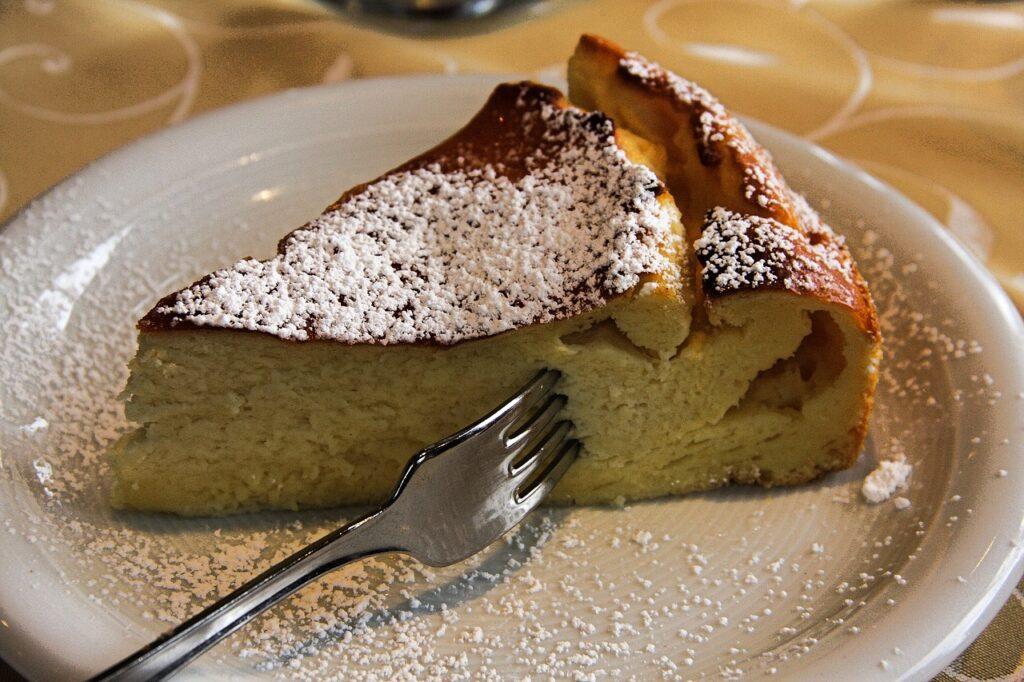Auf einem weißen Teller steht ein Stück Käsekuchen, in dem eine Gabel steckt. Alles wurde mit Puderzucker bestäubt.