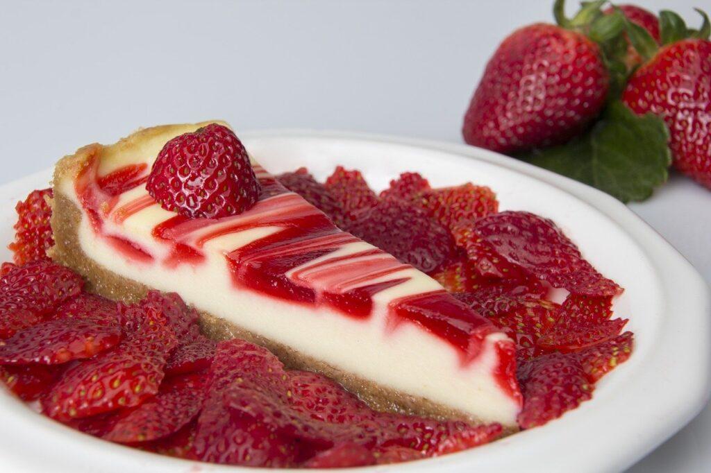 Ein Stück Käsekuchen mit roter Sauce darüber liegt in einem Bett aus Erdbeerscheiben auf einem Teller.