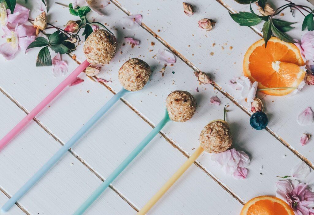 Auf einem weißen Holzuntergrund liegen verschiedene kleine Energy Balls an bunten Stäbchen, drum herum liegen einige Blätter und Orangenscheiben.