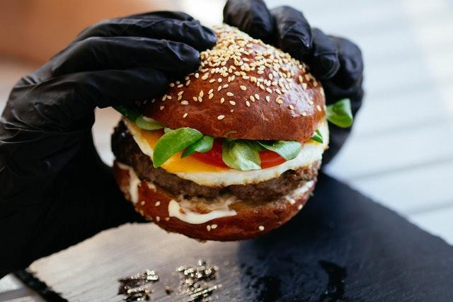 Jemand hält einen fertig belegten Burger mit dunklem Brötchen in seinen beiden Händen.