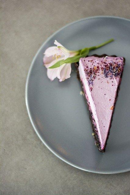 Auf einem grauen Teller liegt ein fliederfarbenes Stück Cheesecake mit einer Blüte.