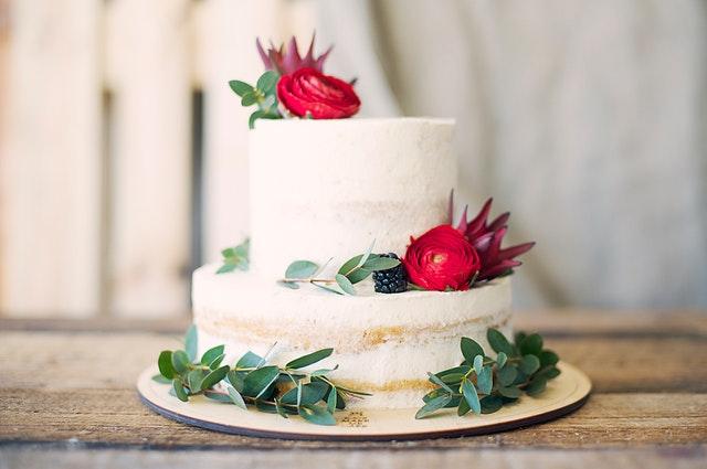 Auf einen zweistöckigen Hochzeitskuchen mit weißer Creme-Ummantelung liegen rote Blüten, grüne Eucalyptuszweige und dunkle Brombeeren als Deko.