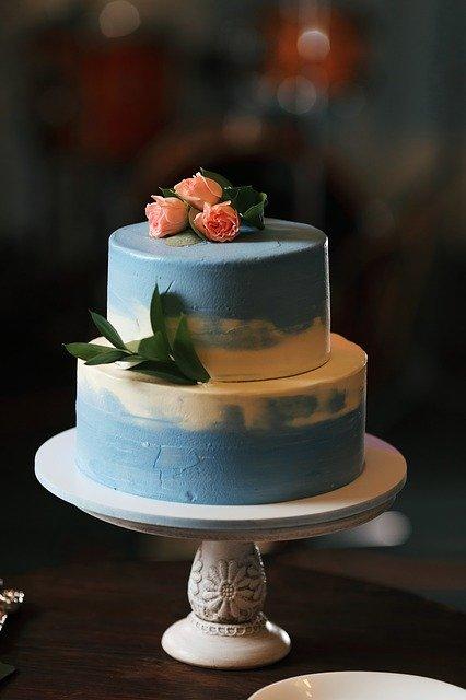 Auf einer Kuchenplatte steht ein zweistöckiger Hochzeitskuchen, der hellblau eingefärbt wurde.