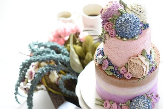 Ein üppig mit Blüten dekorierter Hochzeitskuchen in pastellfarbene Sahne gehüllt