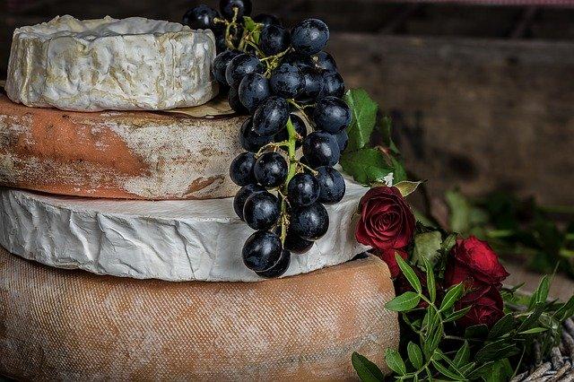 Eine Torte aus mehreren Käselaibern, auf der Weintrauben und Blüten dekoriert sind.