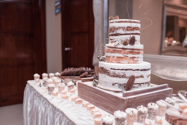 Ein Naked Cake steht als Hochzeitskuchen auf dem Buffet, umringt von kleinen dazu passenden Cupcakes