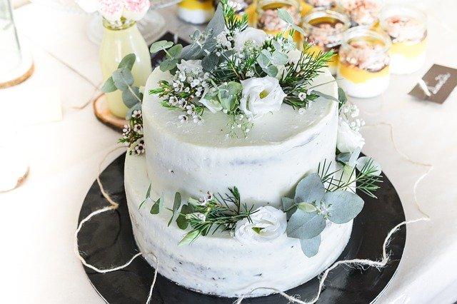 Auf einem schwarzen Teller steht ein zweistöckiger Hochzeitskuchen, der mit verschiedenen blauen und grünen Blumen und Blättern dekoriert ist.
