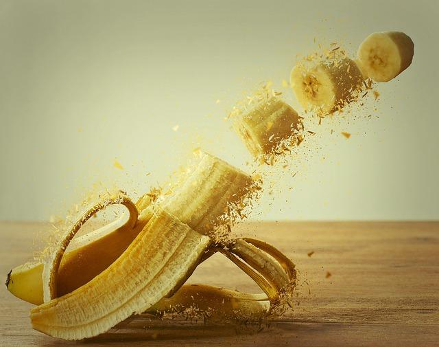 Eine Banane ist halb geschält und liegt auf einer Holzoberfläche. Sie ist in mehrere Teile geschnitten, welche stückweise wegfliegen.
