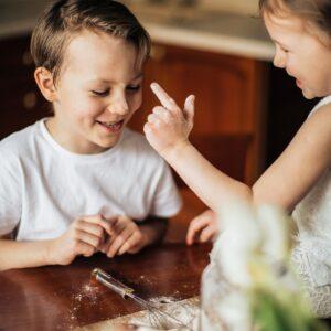 Ein Kind malt einem anderen Kind mit Dinkelmehl einen weißen Punkt auf die Nasenspitze.