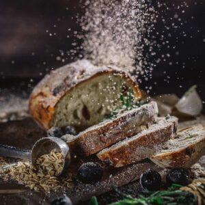 Auf einen zur Hälfte in dicke Scheiben geschnittenen Brotlaib rieselt Mehl.