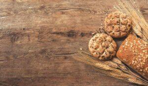 Zwei Brötchen und ein Laib Brot liegen neben Weizenähren auf einem Holztisch.