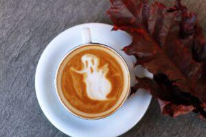In einer Kaffeetasse ist ein weißer Geist im Milchschaum zu erkennen.