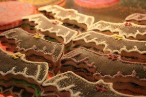 Mehrere mit Schokolade und Lebensmittelfarbe verzierte Kekse in Fledermaus-Form liegen nebeneinander.