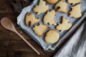 Ein mit Backpapier ausgelegtes Bleck, auf dem Kekse in Geister- und Hexenform liegen.
