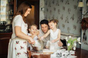 Zwei Erwachsene und zwei Kinder stellen in einer Kühe Salzteig in einer silbernen Schüssel her.