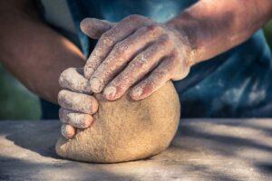 Zwei kräftige Hände kneten eine große Kugel Salzteig auf einem Holztisch.