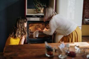Eine Erwachsene und ein Kind schauen in einen Ofen, in den sie ein Blech mit Salzteig schieben.