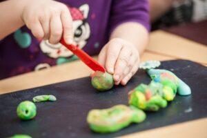 Ein kleines Kind schneidet mit einem Bastelmesser farbigen Salzteig durch.