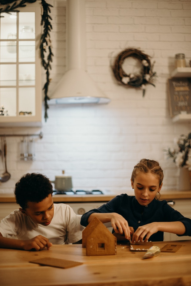Zwei Kinder sitzen an einem Küchentisch und bauen ein Pfefferkuchenhaus.