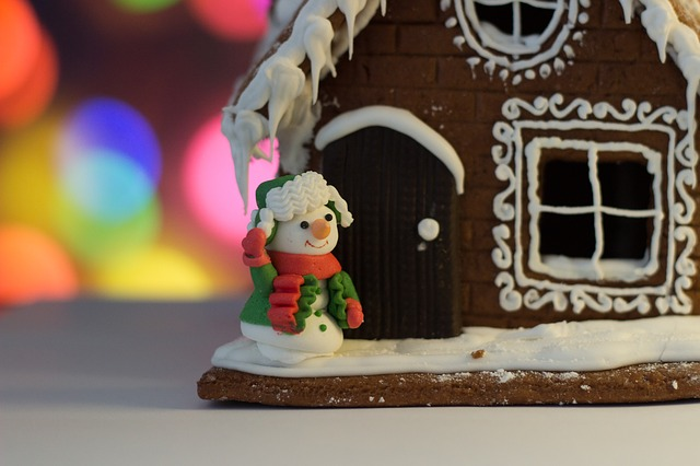 Um die Fenster eines Pfefferkuchenhauses sind mit weißem Zuckerguss Dekoriationen gemalt worden. Davor steht ein Schneemann.