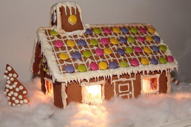 Ein von innen erleuchtetes Pfefferkuchenaus hat mit Zuckerguss kleine Eiszapfen am Dach gemalt bekommen.