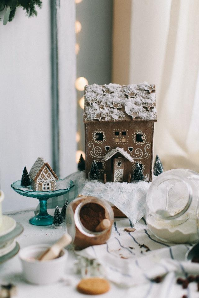 Auf einem mit Backutensilien versehenen Tisch stehen zwei unterschiedlich große, mit weißem Zuckerguss dekorierte Pfefferkuchenhäuser.