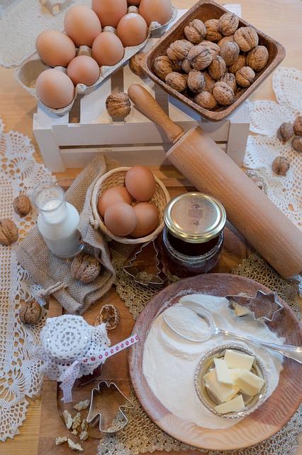 Auf einem Tisch liegen verschiedene Backzutaten und -utensilien verteilt.