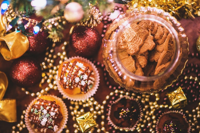 Auf einem weihnachtlich dekorierten Tisch steht ein Vorratsglas mit Gewürzspekulatius darin.