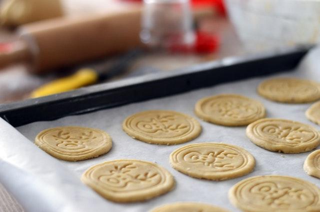 Auf einem Backblech liegen noch ungebackene helle Kekse, die weihnachtlich geprägt sind