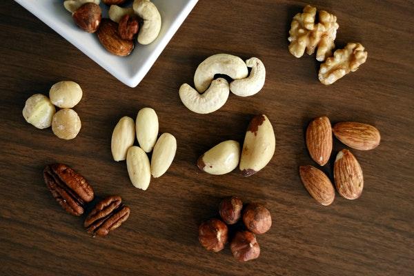Man sieht verschiedene Nüsse beieinander liegen, gruppiert nach Sorten.