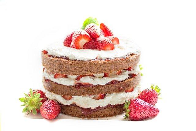 Eine Torte mit drei Biskuitböden ist zu sehen. Zwischen den Schichten befinden sich Creme und Erdbeeren
