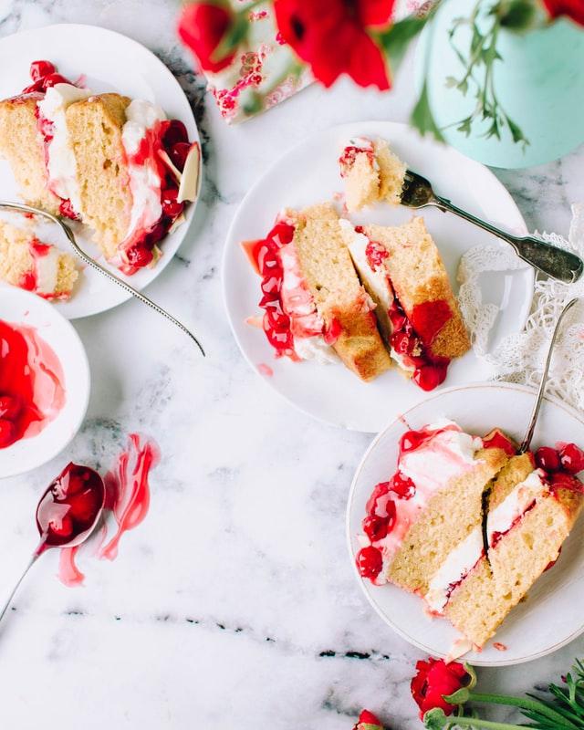 Auf verschiedenen Kuchentellern liegen seitlich Kuchenstücke aus Biskuitböden und Kirschkompott.