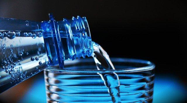 In ein Glas wird sprudelndes Mineralwasser aus einer Flasche eingegossen.