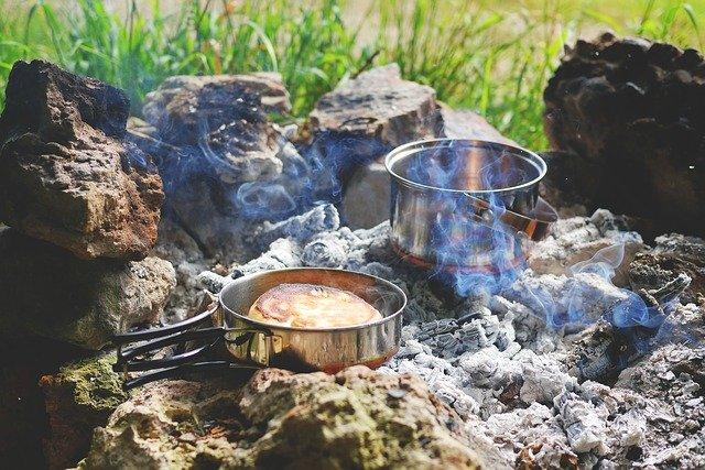Auf einer offenen Feuerstelle stehen zwei Edelstahltöpfe, in einem bäckt ein Brot