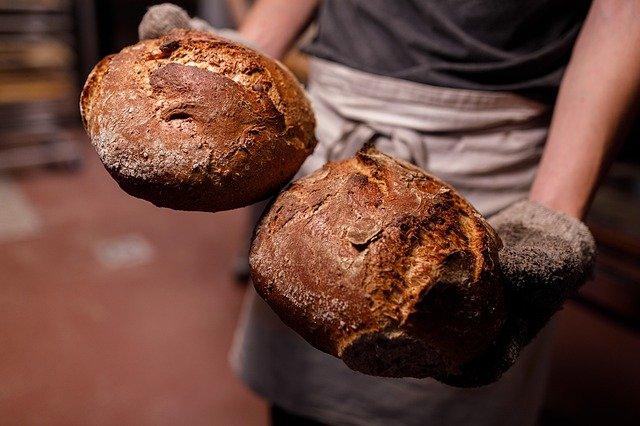 Ein Bäcker hält zwei frischgebackene runde Brot in seinen Händen.