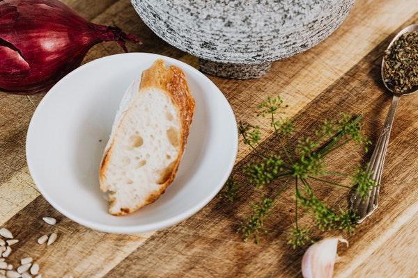 Auf einem Holztisch steht ein Mörser mit Gewürzen darin, daneben steht eine Schüssel mit einer Scheibe Brot
