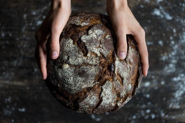 Zwei Hände halten ein frisch gebackenes, rundes, dunkles Brot.