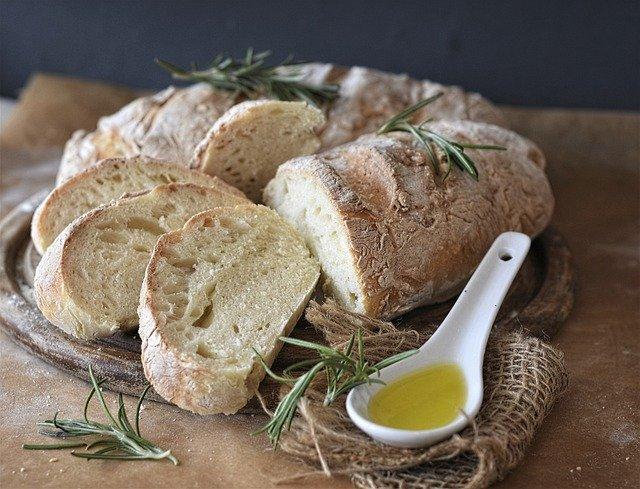 Auf einem Holzbrett liegt ein Ciabatta mit kleinen Rosmarinzweigen, daneben ist ein Löffel voll Olivenöl platziert