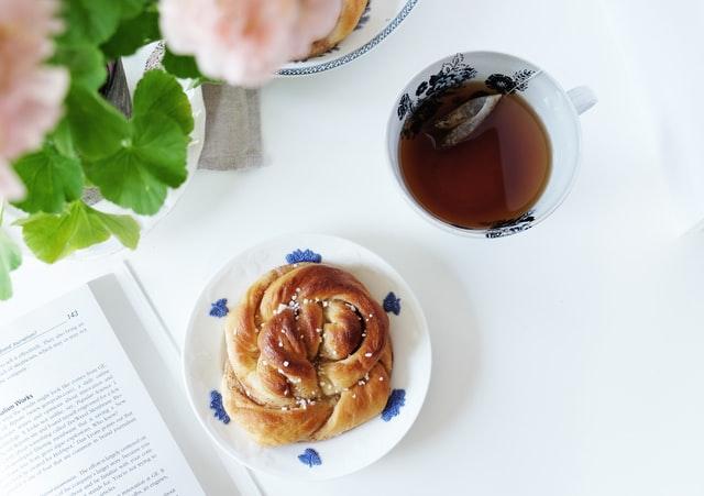 Auf einem Tisch steht eine Pflanze, eine Tasse Tee, ein aufgeschlagenes Buch und ein Teller mit einer Zimtschnecke