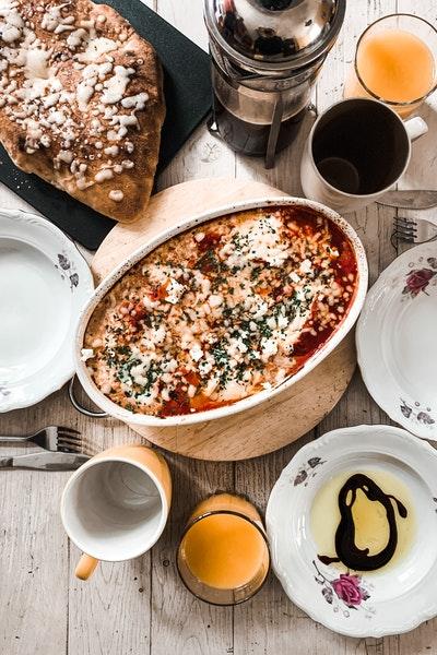 Ein Tisch ist gedeckt mit zwei Tellern, Tassen, in der Mitte steht ein Auflauf, daneben liegt ein Brot.