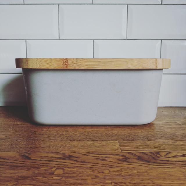 Ein grauer Brotkasten mit einem Holzdeckel steht auf einer Küchenarbeitsfläche.
