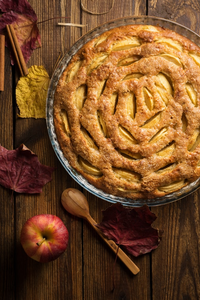 Auf einem Holztisch steht ein Kuchen mit Äpfeln, daneben liegen Blätter
